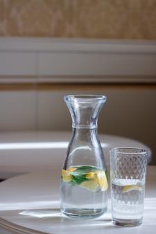 Close-up van een fles met een dop en een glas water met munt en limonade een witte tafel en zon schittering