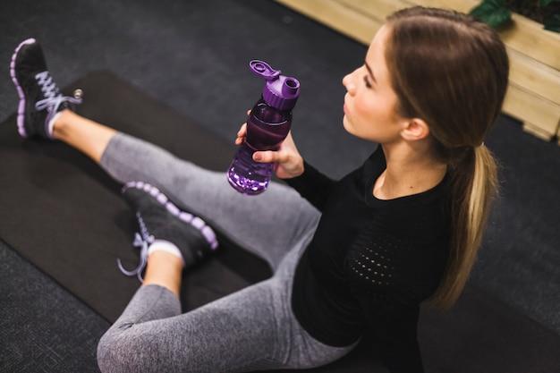 Close-up van een fles van het water van de vrouwenholding in gymnastiek