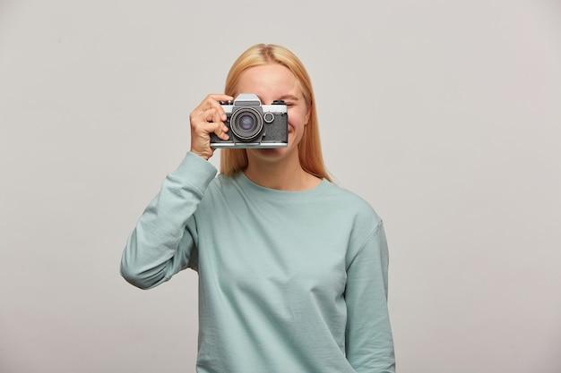 Close up van een fotograaf die haar gezicht bedekt met de retro vintage camera