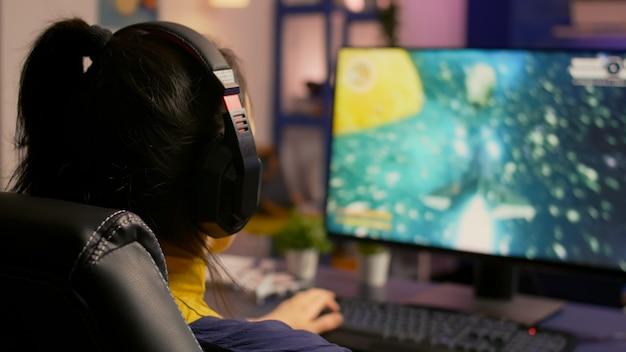 Close-up van een gamer die op een gamestoel zit en een ruimteschieter online videogame speelt voor een virtueel toernooi. speler man met koptelefoon streaming games in een kamer met neonlicht en moderne apparatuur modern
