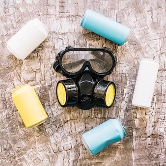 Close-up van een gasmasker omgeven door kleurrijke blikjes