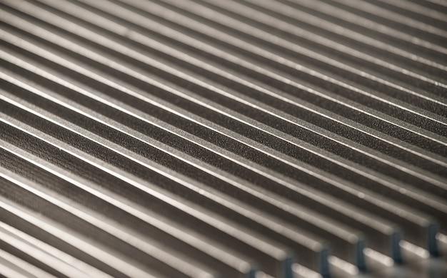 Close-up van een gecanneleerd metalen oppervlak naast een bedieningspaneel op een niet-geïdentificeerd automatisch bedieningsapparaat in een fabriek