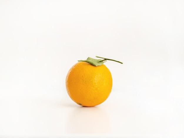 Close-up van een geïsoleerde hele sinaasappel met een blad op een heldere lichtroze achtergrond
