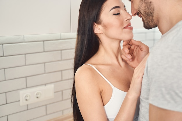 Close-up van een gelukkig jong stel dat dicht bij elkaar in de keuken staat voordat ze een kus krijgen