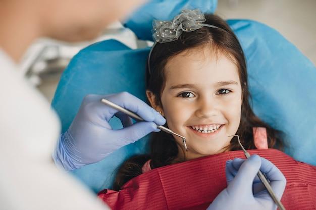 Close up van een gelukkig klein meisje camera kijken voordat tanden onderzoek in een pediatrische stomatologie.