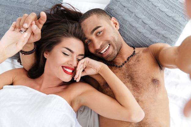 Close-up van een gelukkig romantisch stel dat foto's maakt met de telefoon in bed