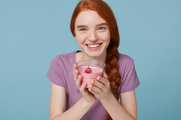 Close-up van een gelukkig roodharig meisje met vlechtglimlach houdt cutely een glas kersenyoghurt in haar handen