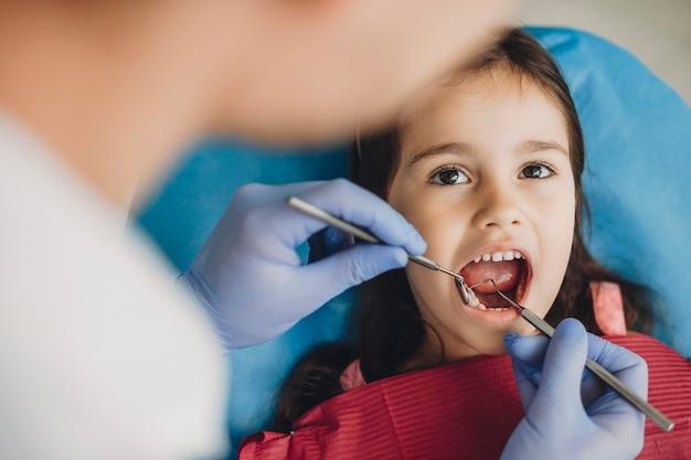 Close up van een gelukkig schattig kind doet een tandonderzoek in een pediatrische stomatologie.