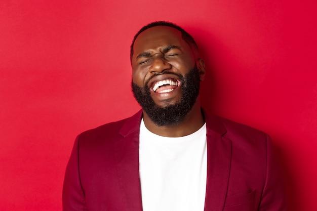 Close-up van een gelukkige en zorgeloze zwarte man die plezier heeft, lacht en glimlacht, staande in blazer tegen rode achtergrond