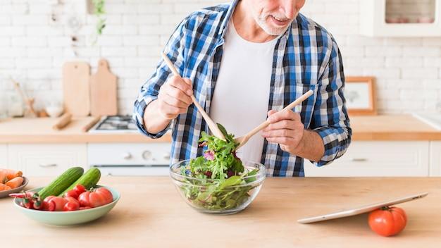 Close-up van een gelukkige hogere mens die de salade in de keuken voorbereidt