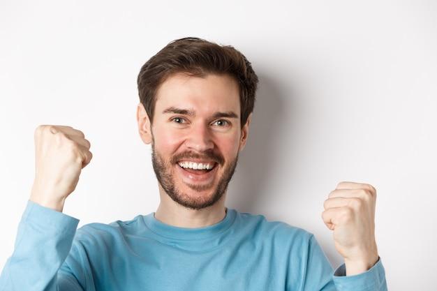 Close-up van een gelukkige jonge man die viert, prijs wint en ja zegt, tevreden glimlachend met vuistpompen, staande op een witte achtergrond