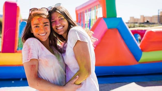 Close-up van een gelukkige jonge vrouwen met holi kleur op hun gezicht omarmen