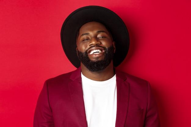 Close-up van een gelukkige knappe zwarte man die naar je lacht, tevreden kijkt, zwarte hoed en blazer draagt, rode achtergrond