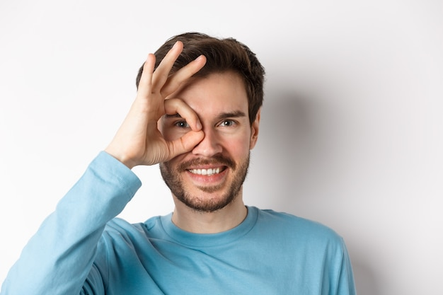 Close-up van een gelukkige man die door een goed teken kijkt en glimlacht, goedkeurt en iets goeds leuk vindt, staande op een witte achtergrond