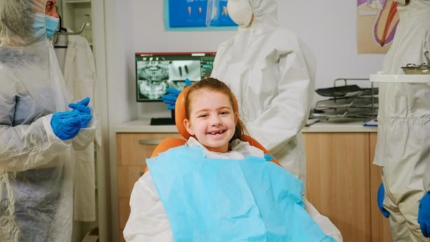 Close-up van een gelukkige meisjespatiënt die lacht om de camera die de tandarts bezoekt tijdens de wereldwijde pandemie, wachtend op een pediatrische stomatoloog. medisch team met pbm-pak, gezichtsmasker, handschoenen die het kind onderzoeken