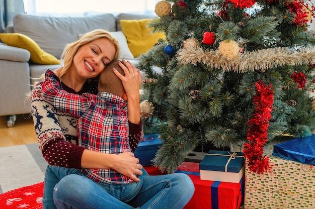 Close-up van een gelukkige moeder die haar zoon knuffelt, kerststemming in een gezellig huis