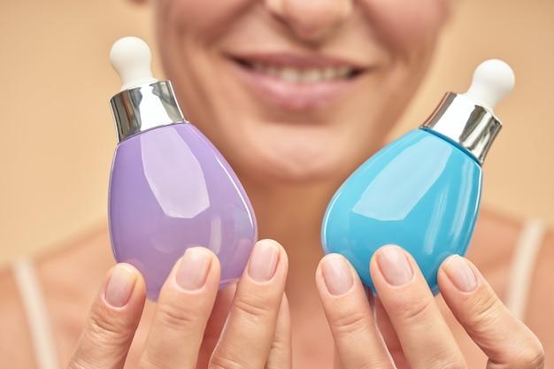 Close-up van een gelukkige volwassen vrouw die potten serum vasthoudt om de huid te hydrateren