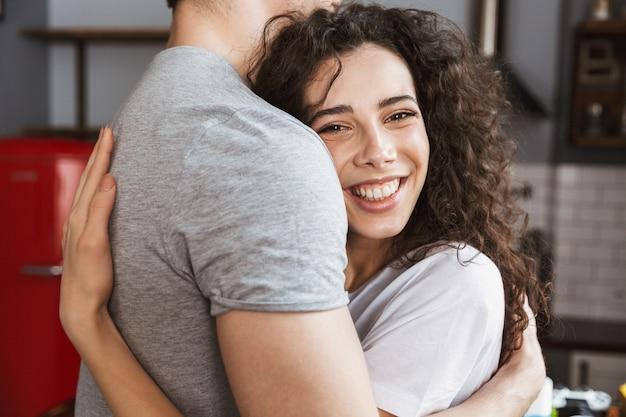 Close up van een gelukkige vrouw die haar vriendje knuffelt in de woonkamer