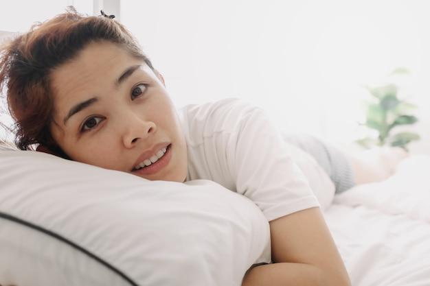 Close-up van een gelukkige vrouw wordt gewoon wakker in de warme ochtend van de zomer
