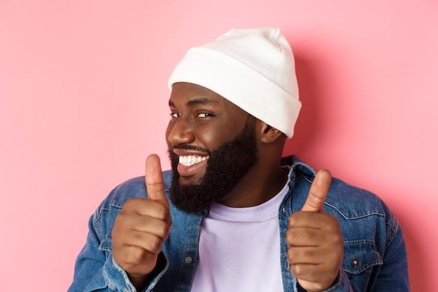 Close-up van een gelukkige zwarte bebaarde man in een muts die steun toont, iets eens is of goedkeurt, slinks giechelt en duimen laat zien, staande over roze achtergrond