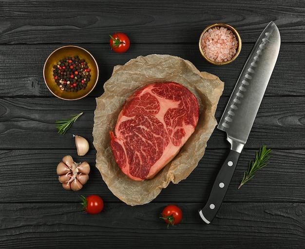 Close-up van een gemarmerde rauwe ribeye biefstuk op bruin papier, met mes en kruiden, over zwarte houten tafel, verhoogde bovenaanzicht, direct erboven