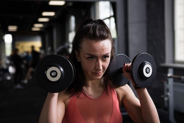 Close up van een gerichte vrouwelijke atleet die traint met halters