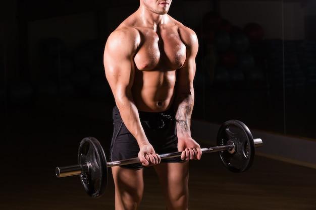 Close-up van een gespierde jonge man gewichtheffen op donkere muur