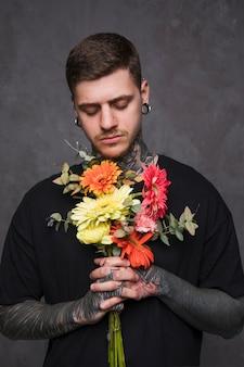 Close-up van een getatoeëerde jonge man met bloemen in hand bidden