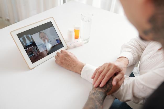 Close-up van een gezin van twee dat aan tafel zit en online met een arts praat via een digitale tablet
