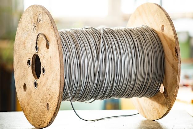 Close-up van een gigantische streng grijze draden op een houten haspel bij de vervaardiging van elektrische apparatuur. het concept van moderne technologie en industriële volumes