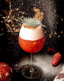 Close up van een glas citrus cocktail versierd met pijnboom bladeren