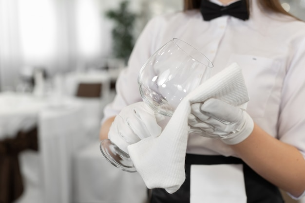 Close-up van een glas en een handdoek in de handen van een ober. voorbereiding, tafelschikking.