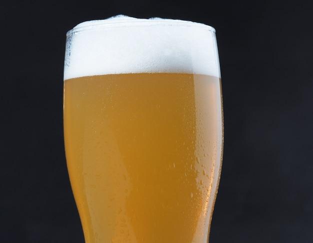Close-up van een glas light bier met schuim. heldere verfrissende alcoholische drank