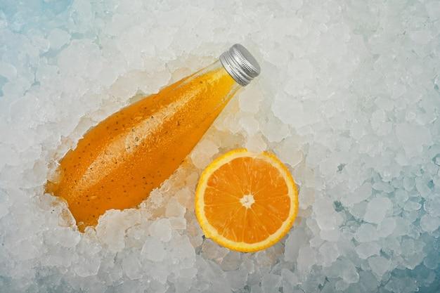Close-up van een glazen fles koude jus d'orange cocktaildrank met chiazaadjes en half gesneden sinaasappel op gemalen ijs op winkelvertoning, verhoogde hoge hoekmening, direct erboven