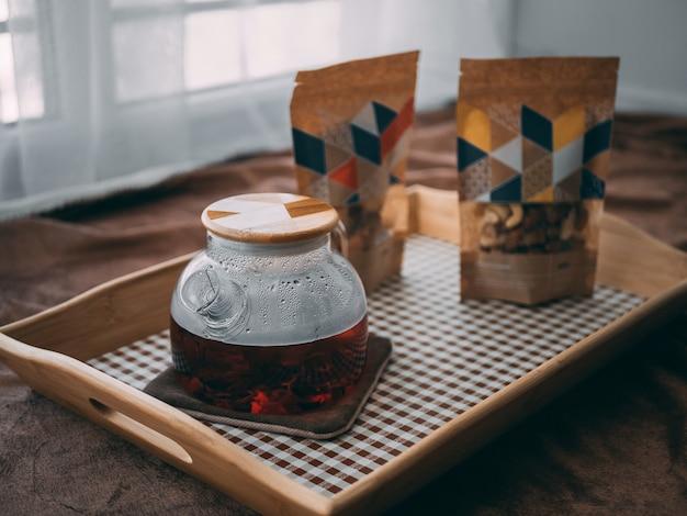Close-up van een glazen pot met een houten dop op een houten dienblad