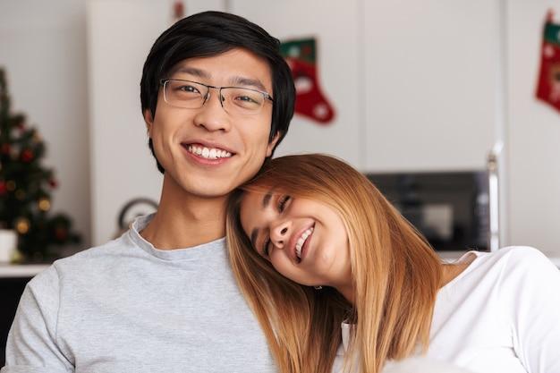 Close-up van een glimlachend jong koppel, knuffelen zittend op een bank thuis