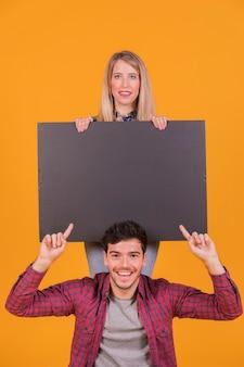 Close-up van een glimlachend jong paar die leeg aanplakbiljet tonen tegen een oranje achtergrond