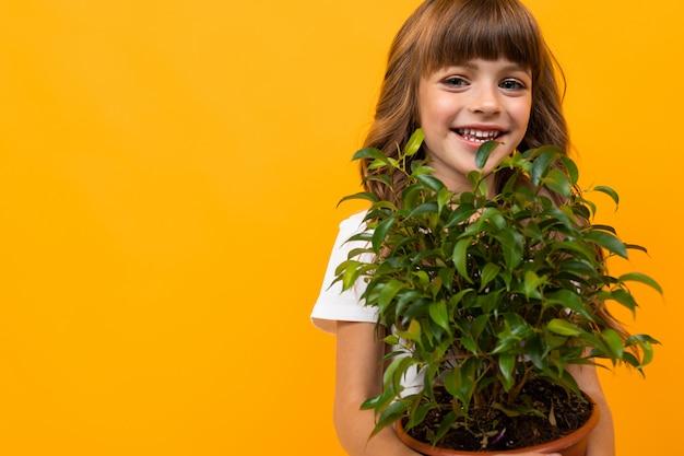 Close-up van een glimlachend meisje met een bloem in een pot op geïsoleerde sinaasappel