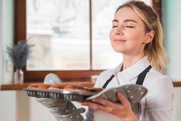 Close-up van een glimlachende jonge vrouw die de verse gebakken muffins ruiken