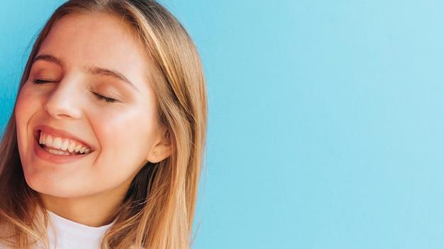 Close-up van een glimlachende jonge vrouw tegen blauwe achtergrond