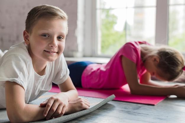 Close-up van een glimlachende jongen die camera bekijkt die dichtbij het uitgeputte meisje ligt