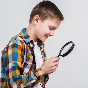 Close-up van een glimlachende jongen die door een vergrootglas kijkt