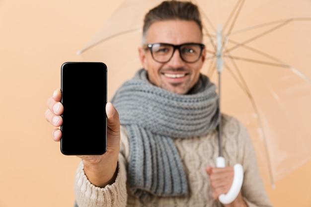 Close-up van een glimlachende man met lege scherm mobiele telefoon terwijl staande onder paraplu geïsoleerd over beige muur