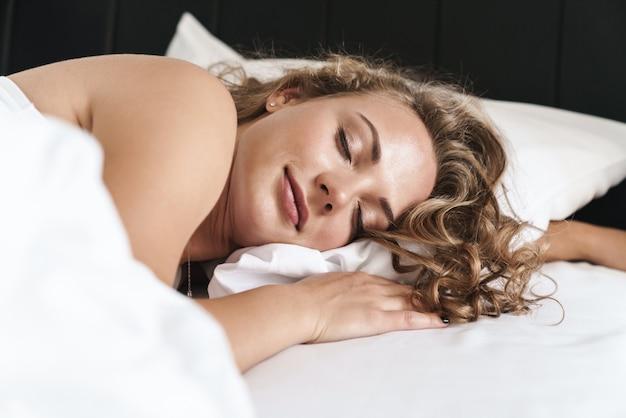 Close-up van een glimlachende mooie jonge blonde vrouw met een haar die op een kussen in bed ligt, slapend