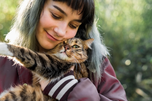 Close-up van een glimlachende mooie vrouw die haar gestreepte katkat in tuin omhelst