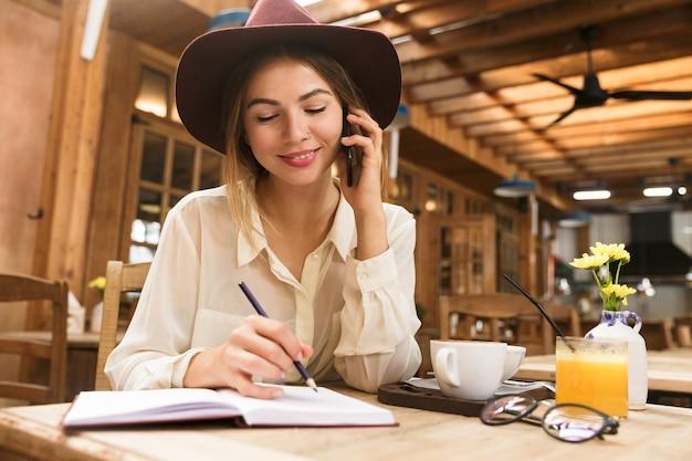 Close up van een glimlachende vrouw in hoed zittend aan de café tafel