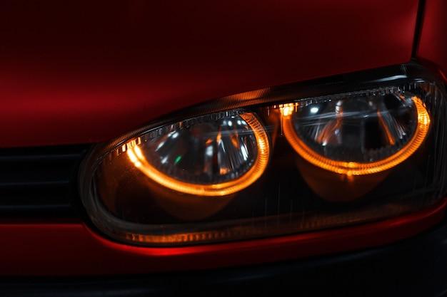 Close-up van een gloeiende led-koplamp en rode auto