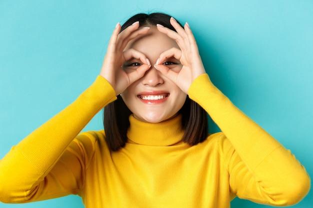 Close-up van een grappig aziatisch meisje dat door een handbril kijkt en glimlacht, promo-aanbieding bekijkt, over een blauwe achtergrond staat