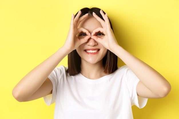Close-up van een grappig aziatisch meisje dat door een verrekijker kijkt en glimlacht, staande in een t-shirt tegen een gele achtergrond.