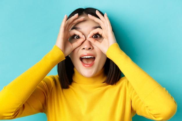 Close-up van een grappige aziatische vrouw die door een verrekijker kijkt met een verbaasd gezicht, iets geweldigs ziet, staande over een blauwe achtergrond